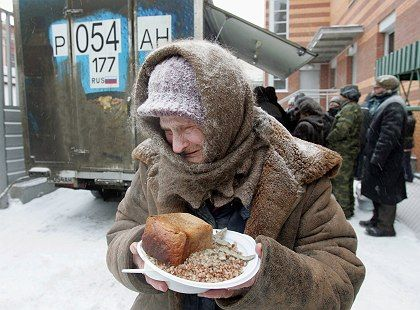 """An elderly woman holds a plate of food she received at a distribution point for homeless people at a train station in Moscow: """"The gap between rich and poor in Russia is scandalous."""""""