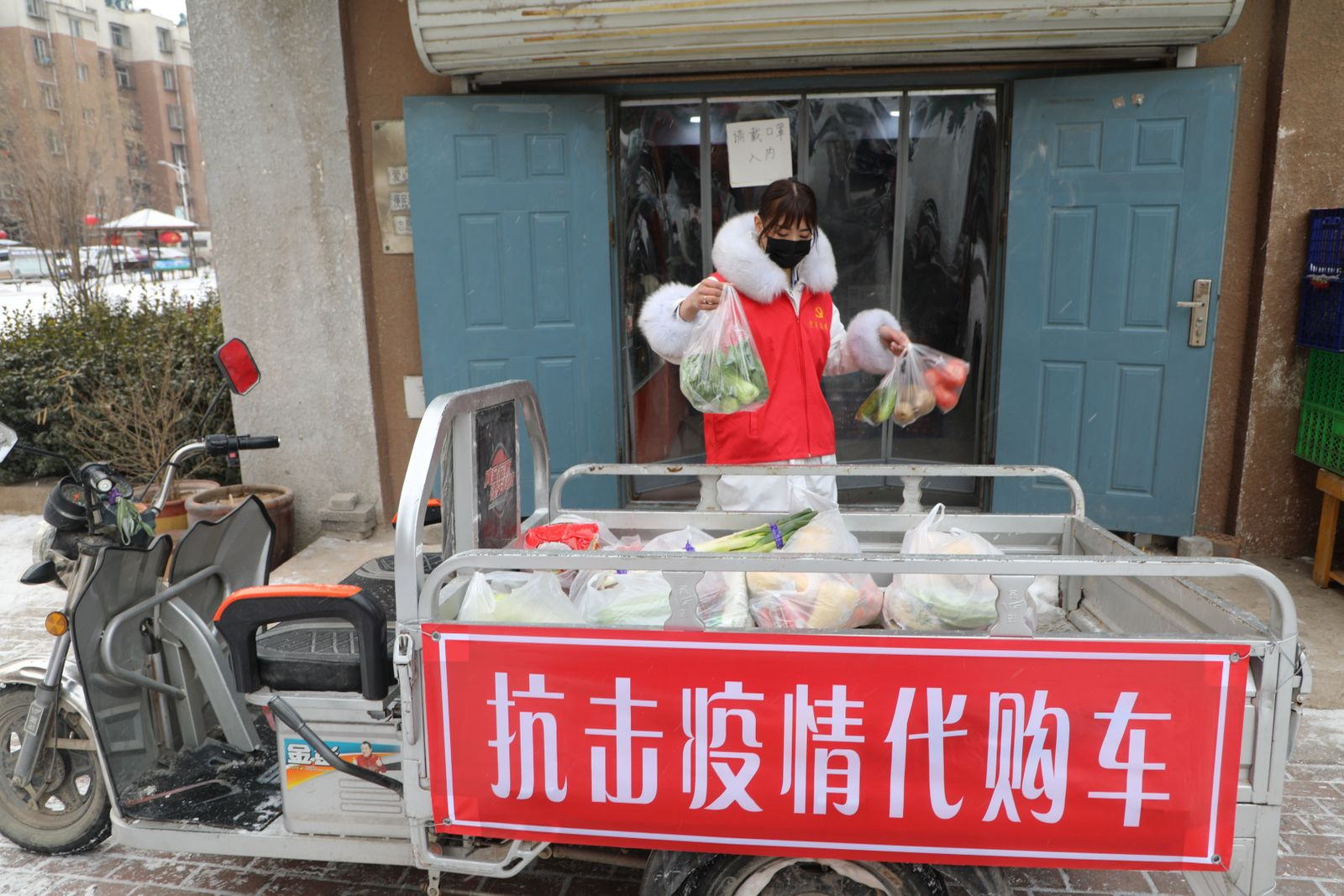 Volunteer helps residents who are affected by the measures to prevent and control the novel coronavirus to purchase daily necessities from a store in Tangshan