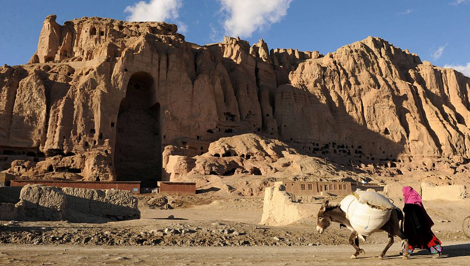 A woman walking past the site of one of the two destroyed Buddha statues in Bamiyan province.