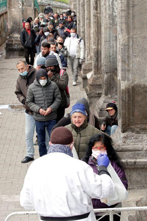 Ein Priester verteilt in Neapel Lebensmittel an Arme