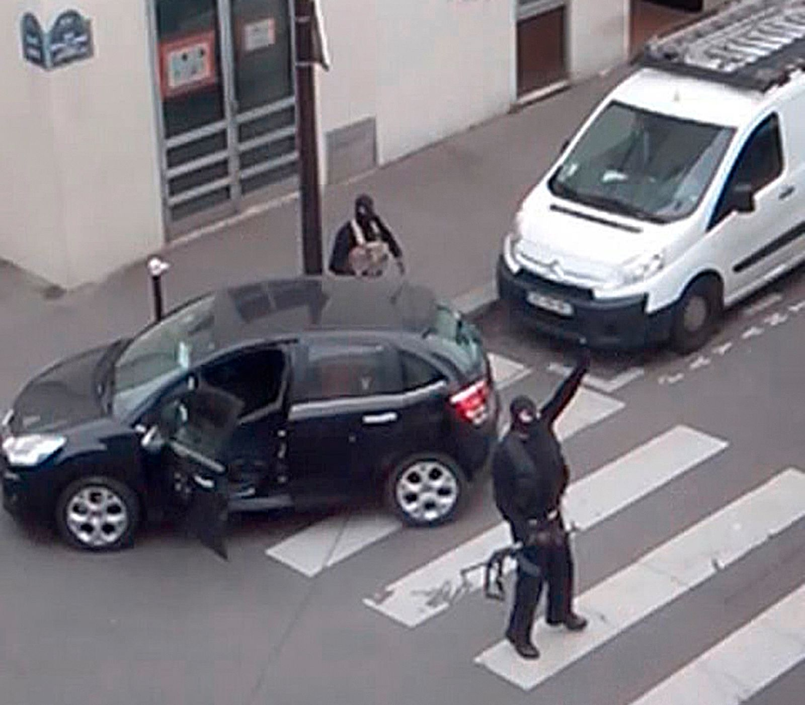 Gunmen gesture as they return to their car after the attack outside the offices of French satirical weekly newspaper Charlie Hebdo