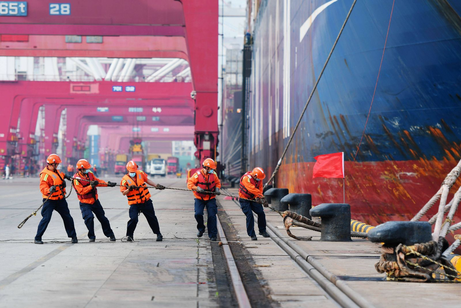 QINGDAO, CHINA - JUNE 02: Dock workers pull the mooring line of a cargo ship at Qingdao Port on June 2, 2020 in Qingdao