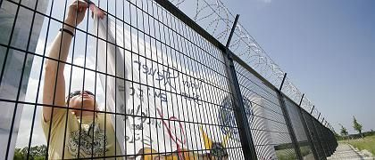 Auf der anderen Seite des Zauns: ein Demonstrant bringt ein Plakat am Sicherheitsbollwerk um Heiligendamm an