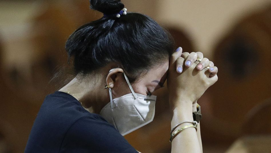 Eine Frau mit Atemschutzmaske betet während einer Messe. Die Zahl der Infektionen und Todesopfer durch die Lungenkrankheit aus China ist weltweit erneut gestiegen.