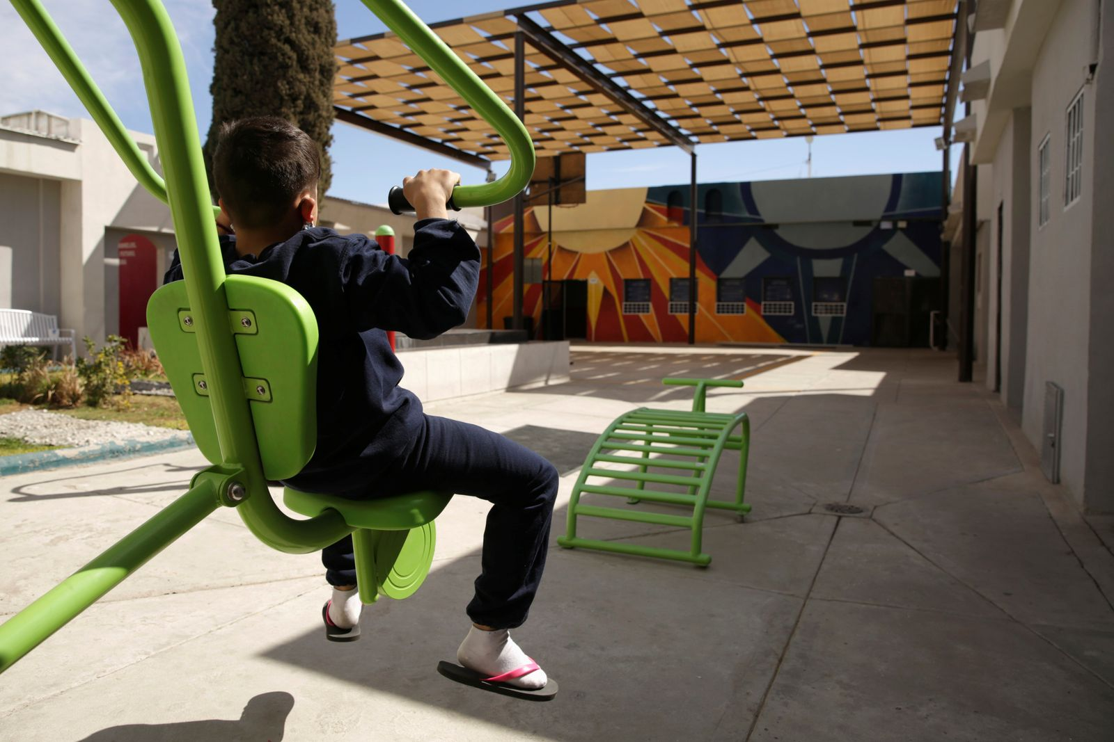 A migrant child exercises in a recreation area at the Noemi Alvarez Quillay immigrant shelter for unaccompanied minors, run by the Mexican government, in Ciudad Juarez