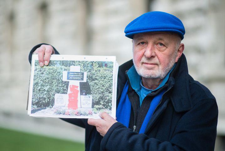 Aktionskünstler Kastner mit einem Foto des rot angemalten Scheingrabs Jodls (Archivbild)
