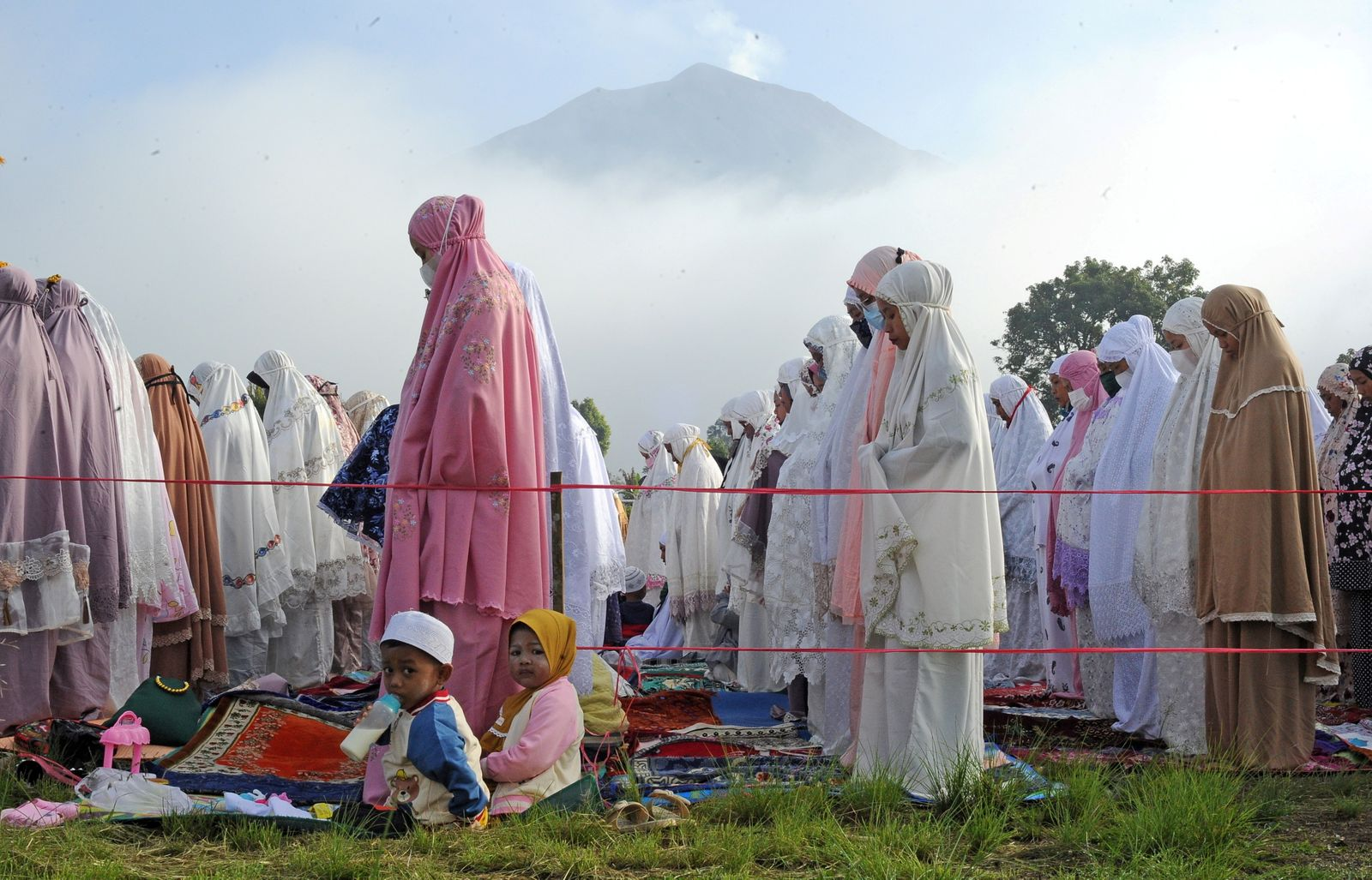 Indonesian Muslims attend a mass prayer session at Gunung Labu field as Mount Kerinci Volcano is seen in the background during Eid al-Fitr, marking the end of the holy fasting month of Ramadan, in West Kayu Aro, Kerinci