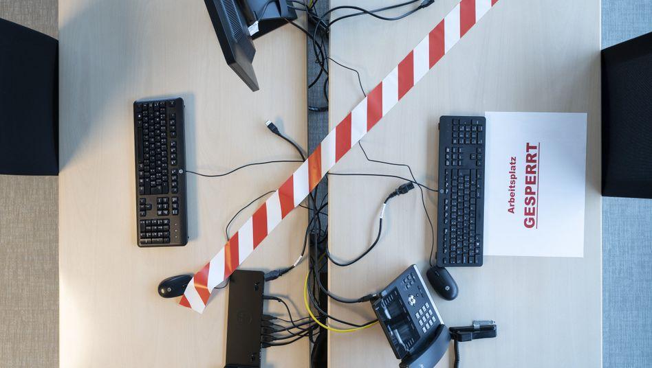 Ein zum Schutz vor Corona-Ansteckungen gesperrter Arbeitsplatz in einem Großraumbüro