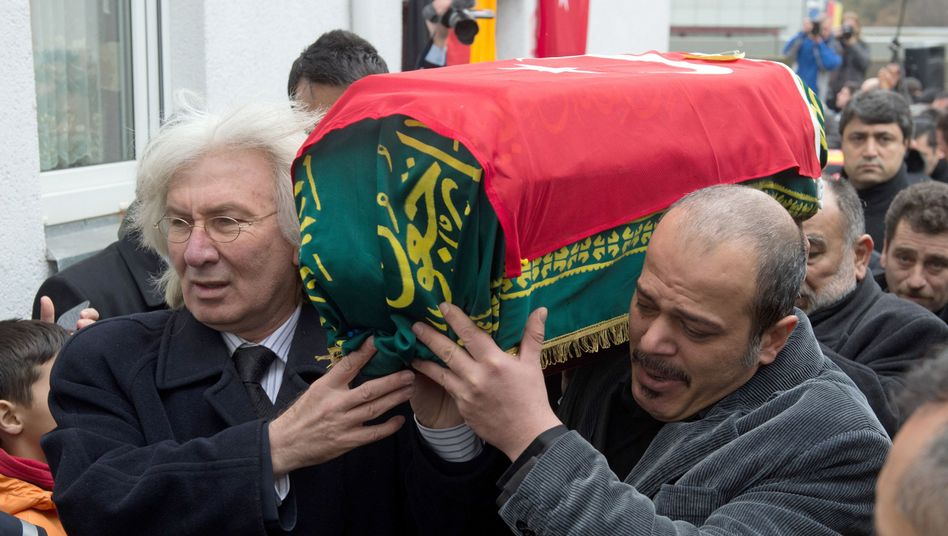 Turkish ambassador Hüseyin Avni Karslioglu (left) carries the coffin of one of the children killed in the fire.