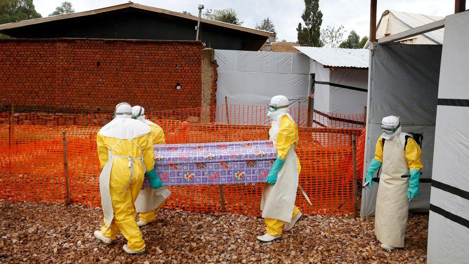 Helfer tragen den Sarg eines Ebola-Opfers aus einem Behandlungszentrum