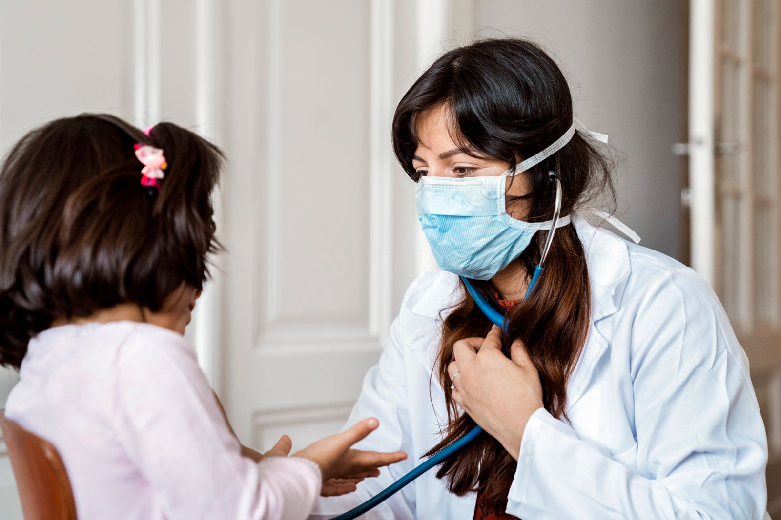 Female doctor examining preschool patient at home