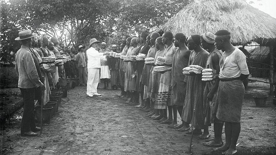 In Reihen angetreten, mussten Arbeiter auf Kautschukplantagen in Ostafrika ihre Arbeitsausbeute abliefern (vor 1914)