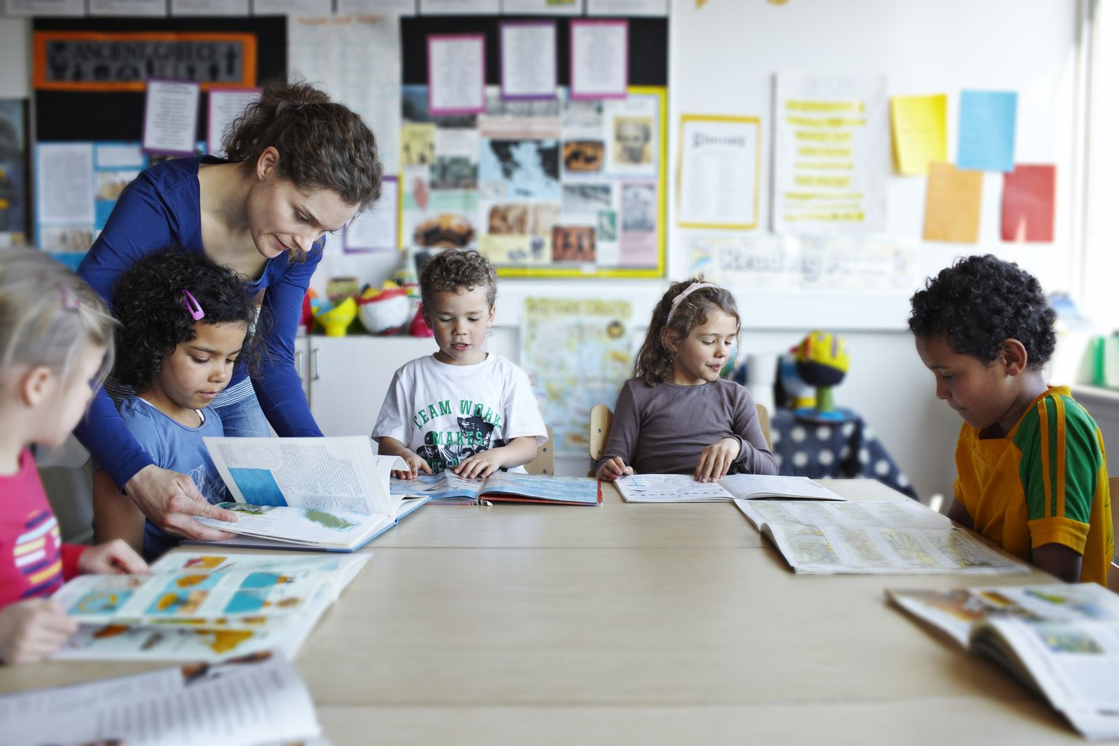 Teacher looking in books with children