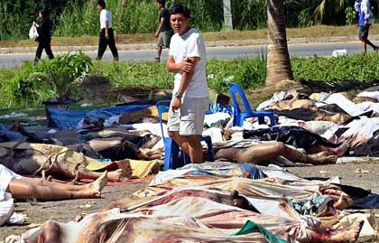 Geschockt wandert ein Überlebender zwischen den Reihen von Toten, die im Nationalpark Khao Lak ums Leben kamen