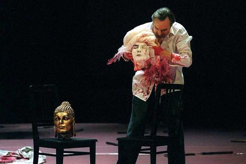 "Scene from ""Idomeneo"" during a rehearsal in 2003: King Idomeneo (played by Charles Workmann) places the severed heads of the Prophet Muhammad on a chair next to the head of Buddha."
