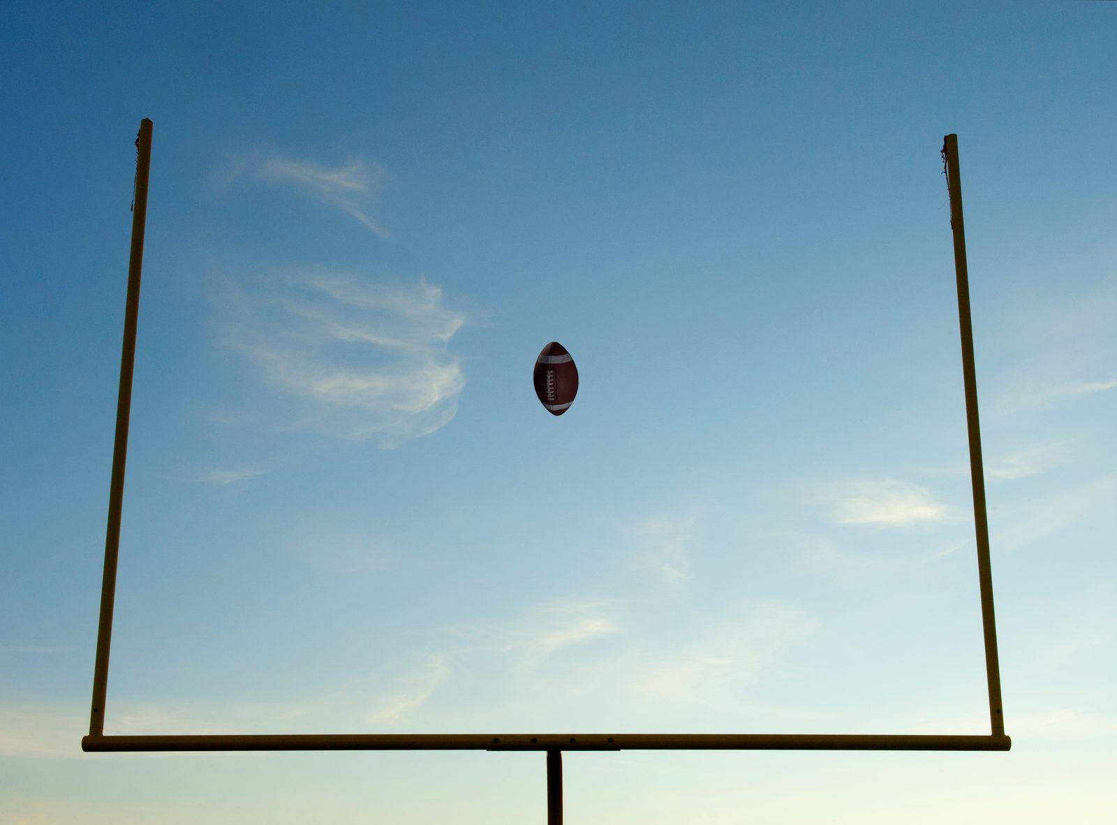 Football being thrown through goal posts