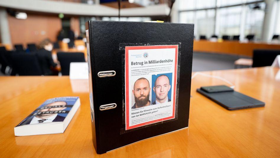Ein Aktenordner mit Fahndungsfotos des früheren Wirecard-Finanzvorstands Jan Marsalek im Sitzungssaal zur Wirecard-Affäre